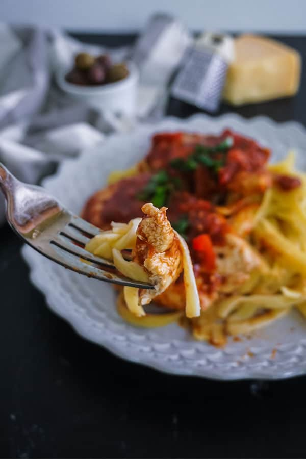 a forkful of Homemade Chicken Cacciatore above more of the food on a  white plate on a table next to a gray and white checkered cloth, a bowl of olives, a mini cheese grater, and a block of cheese