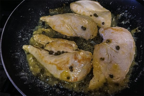 cooking chicken, sauce, capers and lemon juice in a skillet