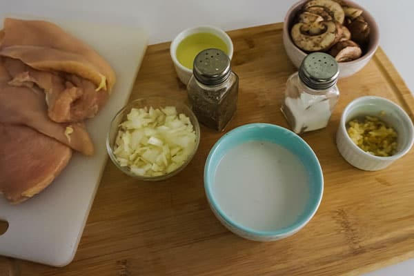raw chicken breasts on a cutting board, bowls of onion, chicken broth, mushrooms, sauce and seasonings on a wood cutting board