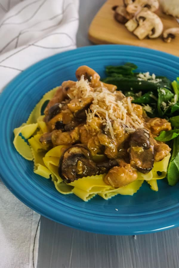 Homemade Chicken Tetrazzini in a blue bowl with mushrooms, on a cutting board in the background