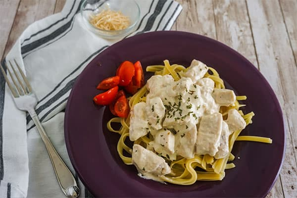 Slow Cooker Alfredo Chicken next to tomatoes on a purple plate next to a fork, black and white cloth, and bowl of shredded cheese, all on a wood table