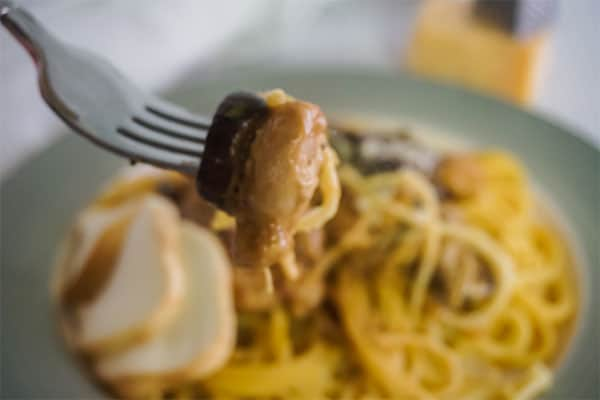 a forkful of Slow Cooker Chicken Tetrazzini with more on a plate blurred out in the background