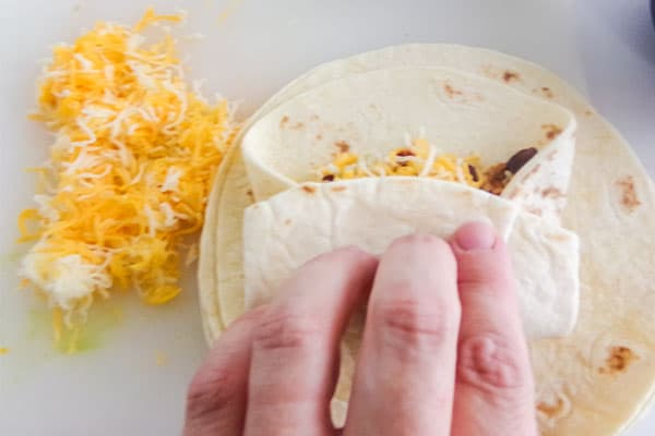 a hand folding up the chicken chimichanga tortilla with shredded cheese next to it