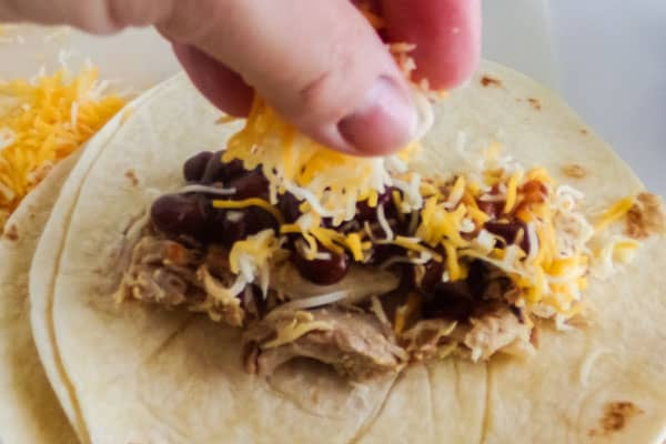 a hand adding shredded cheese to beans on shredded chicken on a flour tortilla with shredded cheese in the background