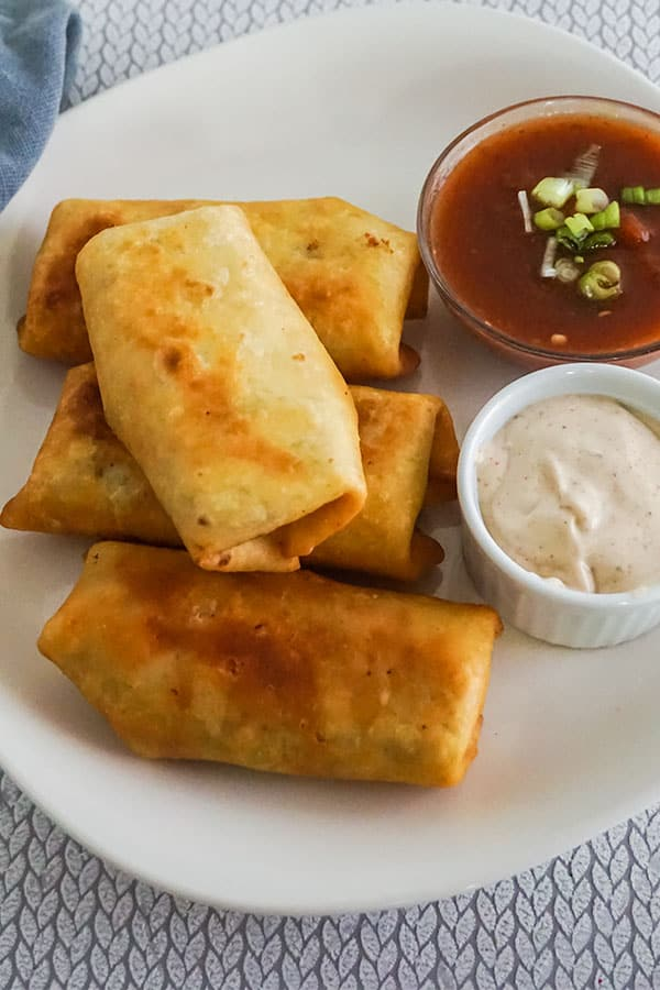 four Chicken Chimichangas on a white plate next to two bowls of sauce