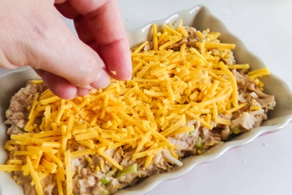 chicken enchilada dip mixture being topped with shredded cheese