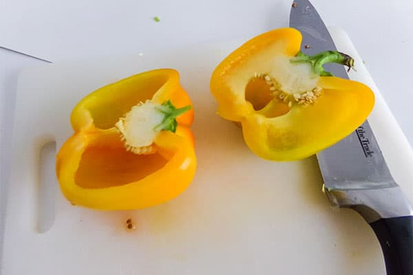 a yellow bell pepper sliced in half on a cutting board next to a knife
