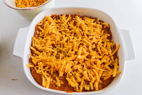 shredded cheese on top of the chicken tamale pie in a white baking dish
