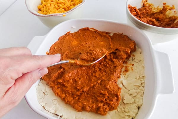 chili being spread over the masa mixture in a white baking dish