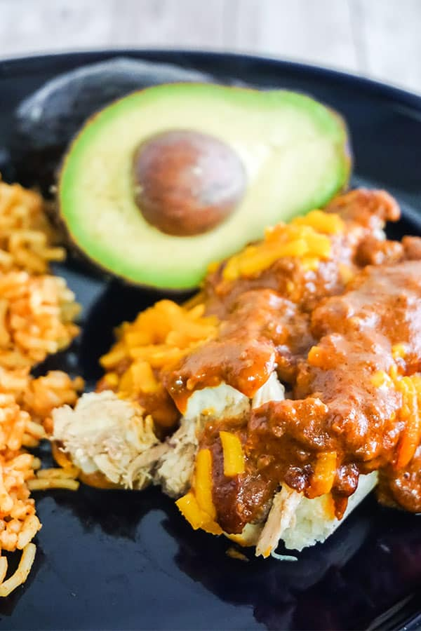 closeup of Chicken Tamale Pie next to rice and half an avocado on a black plate