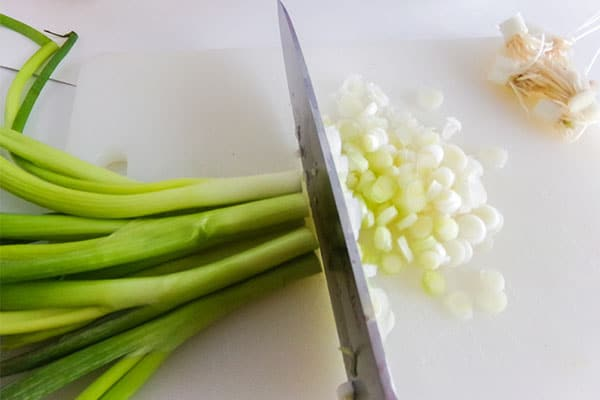 a knife chopping green onions on a white cutting board