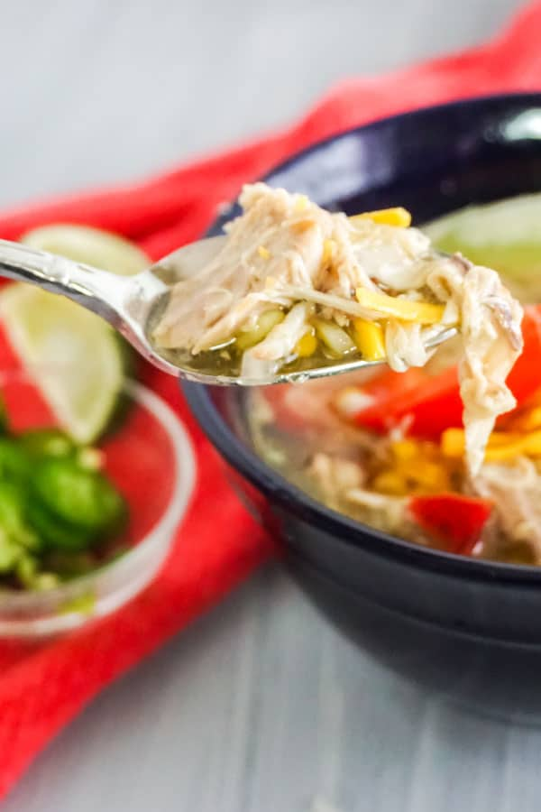 a spoon of Chicken Tortilla Soup above more in a blue bowl on a white table next to a bowl of jalapeno slices and lime slices on a red cloth