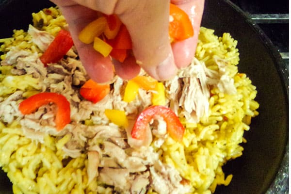 layering bell peppers over chicken and rice in a cast iron skillet