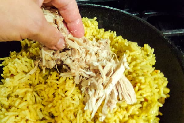 layering chicken over rice in a cast iron skillet