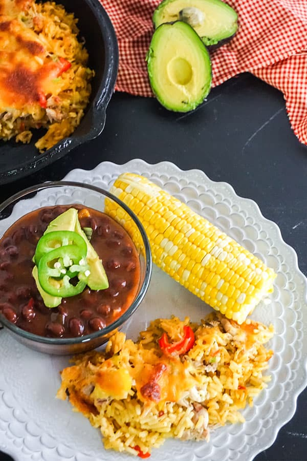 Mexican Chicken and Rice Casserole next to beans and corn on the cob on a white plate on a black table with more casserole. an avocado cut in half and a red and white checkered cloth in the background