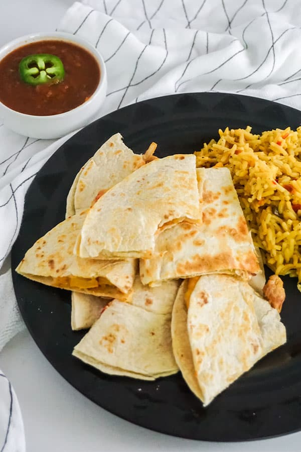 sliced chicken quesadilla next to rice on a black plate on a white and black cloth next to a white bowl of salsa