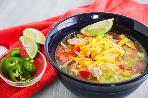 Chicken Tortilla Soup in a blue bowl on a white table next to a bowl of jalapeno slices and lime slices on a red cloth