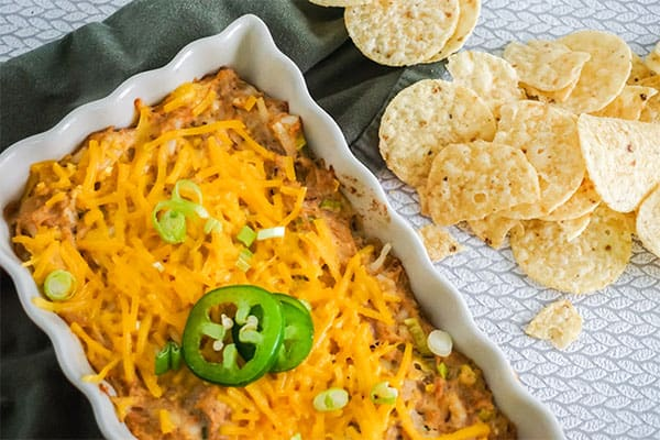 Sour Cream Chicken Enchilada Dip in a white baking dish next to some round tortilla chips on a gray cloth