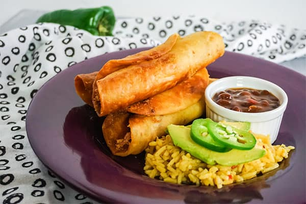 Chicken Taquitos next to rice and beans on a purple plate on a white and black cloth