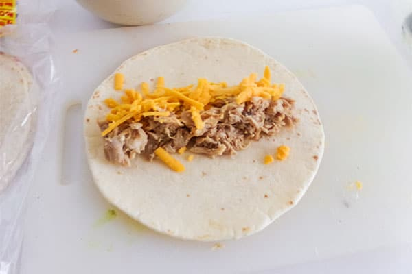 shredded cheese and chicken on a flour tortilla