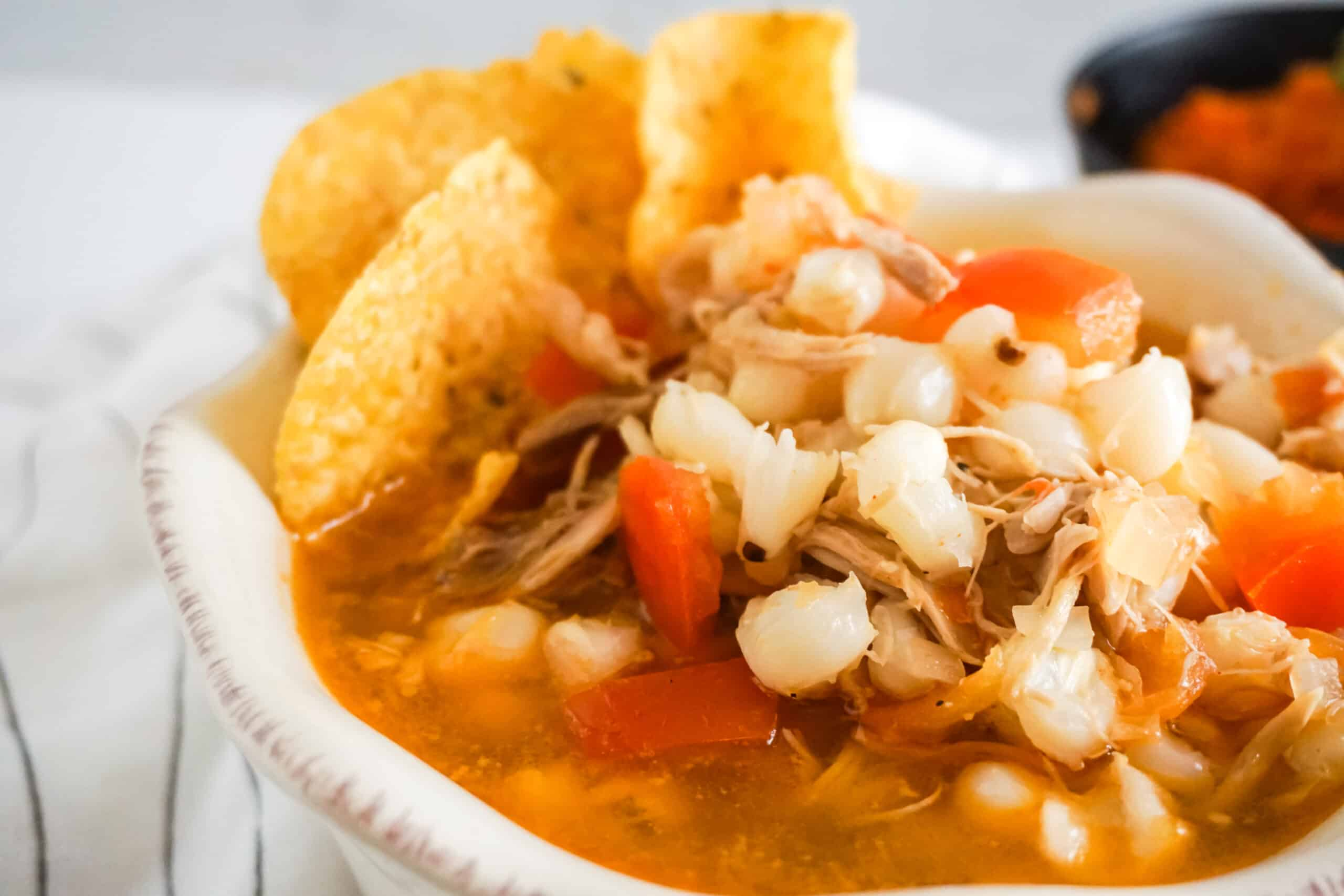 Chicken Posole soup in a white bowl next to rice in a bowl