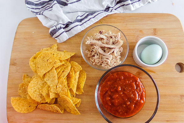 chips, shredded chicken in a glass bowl, tomato sauce in a glass bowl, an egg in a white ramekin, all on a wooden cutting board next to a gray and white cloth