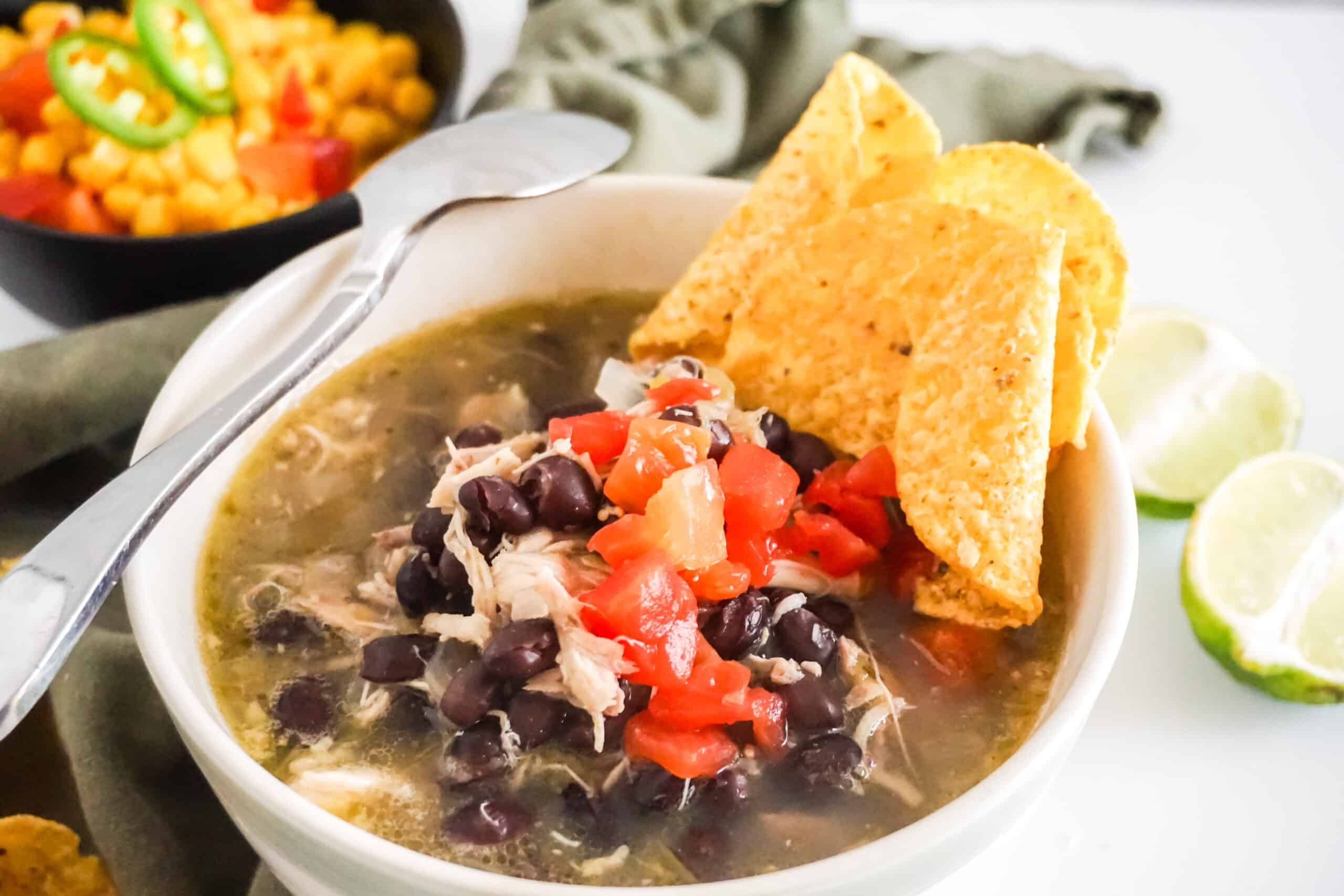 Black Bean Chicken Chile Verde Soup in a white bowl with a spoon on it and a bowl of corn and a green cloth in the background