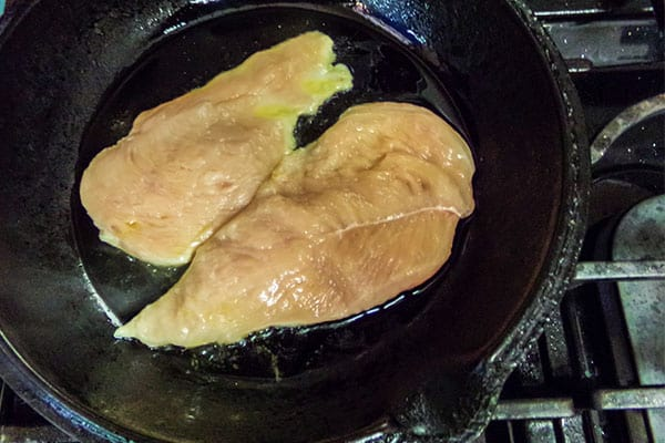 two chicken breasts cooking in oil in a skillet