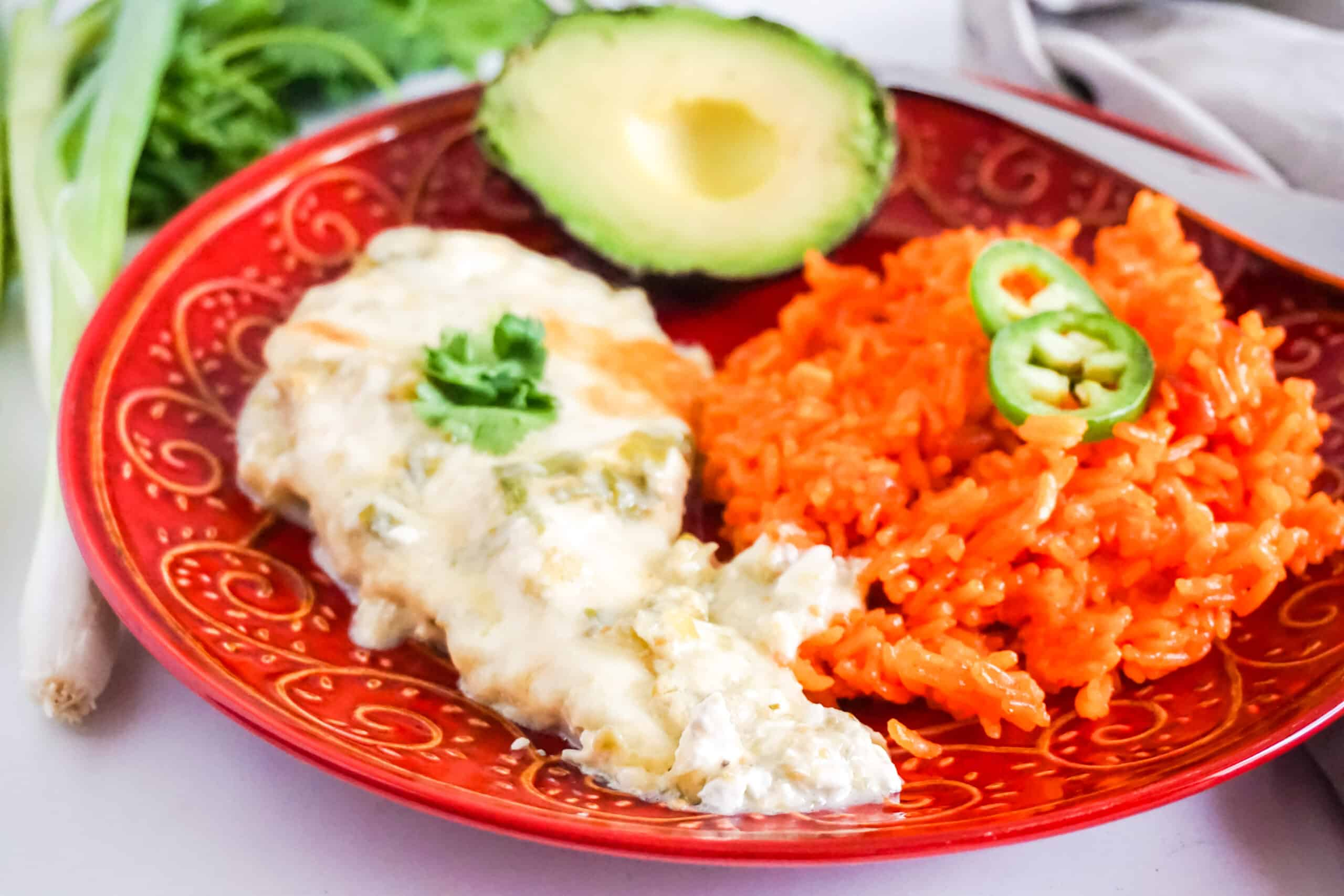 Chicken Chile Verde next to rice and an avocado on a red plate