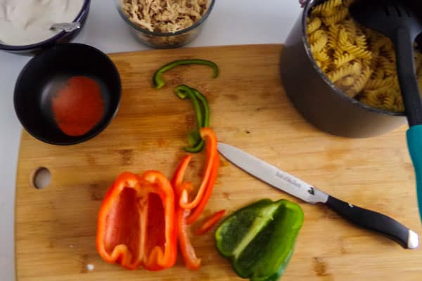 red and green bell pepper sliced on a wooden cutting board next to bowls and a pot of the ingredients needed to make Mexican Chicken Pasta